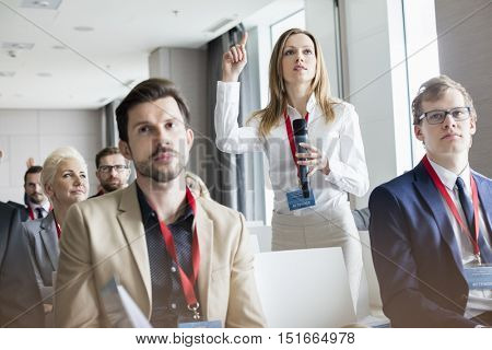 Confident businesswoman asking questions during seminar