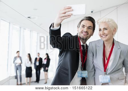 Business people taking selfie in convention center with colleagues walking in background