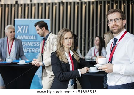 Confident business people holding coffee cups at lobby in convention center