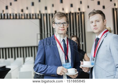 Portrait of confident businessmen holding coffee cups in convention center