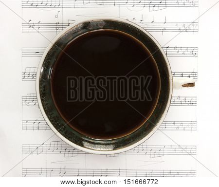 A vintage cup of black coffee, shot from above on a piece of sheet music. Selective focus
