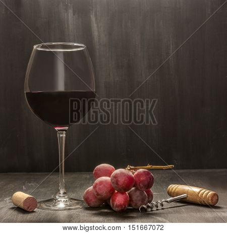A low key photo of a glass of red wine with grapes, vintage corkscrew and a cork, side view on a dark background texture with plenty of copyspace