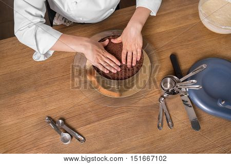 chocolate cake preparing on wooden kitchen table with kitchenware top view
