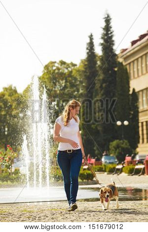 A young woman walking with a beagle dog on a leash near the fountain in the park