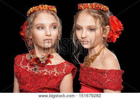 Portrait of a beautiful little girls in red dresses on black background