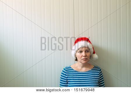 Disappointed woman with Christmas Santa Claus hat suffering from holiday depression sad and lonely woman waiting New Year all let down