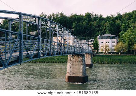 Salzburg Austria - April 29 2015: Mozarts bridge. Old metal bridge over Salzach river. Salzburg was the birthplace of Mozart. It is an Unesco World Heritage Site.