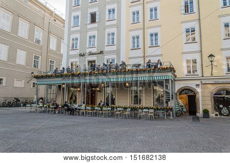 Salzburg Austria - April 29 2015: Terrace of cafe with tourists. Salzburg is renowned for its baroque architecture and was the birthplace of Mozart. It is an Unesco World Heritage Site.