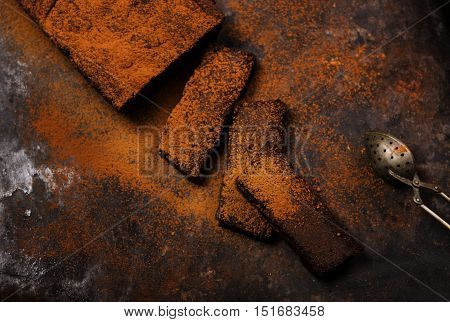 Chocolate flourless cake, dusted with cocoa on a dark rusty metallic background