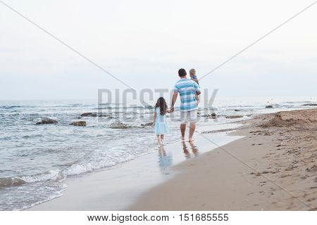 Back view of  young father and his two pretty kids walking along sand beach at evening time