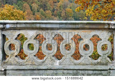 Decorative old gray concrete fence with balustrade and autumn park with trees in the background.