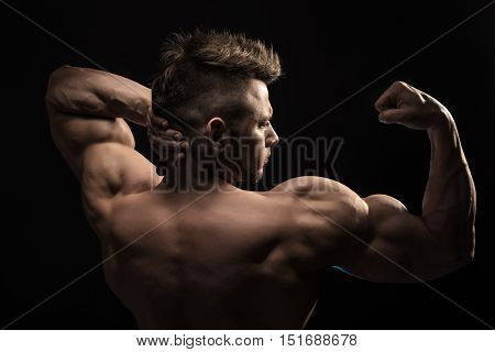 Strong Athletic Man Fitness Model posing back muscles, triceps, latissimus over black background poster