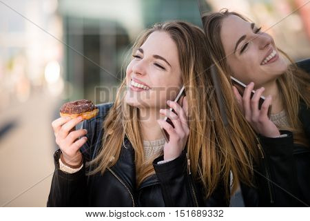 Teen girl eating donut and calling phone - reflection in show window