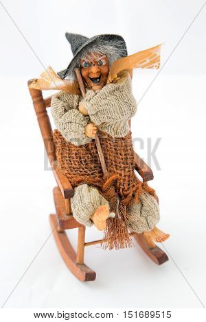 Halloween witch in woden chair with brumstick
