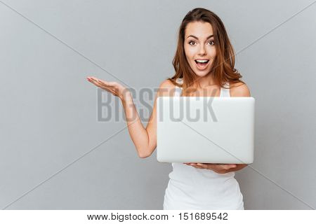 Portrait of a shocked happy woman with laptop holding copy space on palm isolated on a gray background
