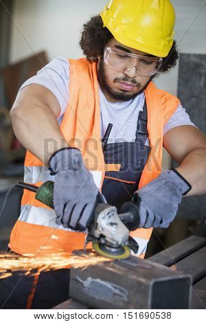 Young manual worker grinding metal in industry