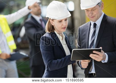 Businessman and businesswoman using digital tablet with colleagues in background at industry