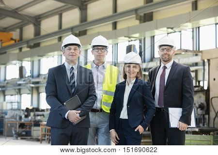 Portrait of confident business people wearing hardhats in metal industry
