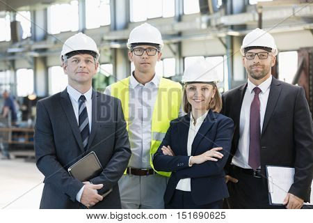 Team of confident business people wearing hardhats in metal industry