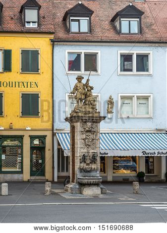 Wurzburg Germany - May 22 2016: Public vintage drinking fountain (water tap) with young fishermen statue on the street of the old town of Wurzburg Lower Franconia Bavaria Germany.