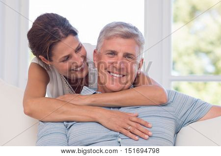 Portrait of young woman embracing father from back and smiling. Happy father and daughter giving a tender hug. Portrait of mature daughter hugging her older father from behind.