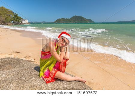 Christmas in the tropics. Beautiful woman with red Santa Claus hat relaxing on rocks in tropical Laem Ka Beach for the Christmas holidays in Phuket, Thailand.