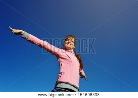Beautiful young woman with arms raised against the blue sky.