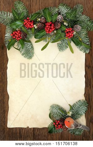 Christmas abstract background border with flora of holly, ivy, mistletoe and snow covered fir with robin decoration on old parchment paper over oak.