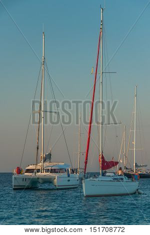 One white catamaran and two sailing yachts are on the anchorage in a bay and they are floodlit with a sunset