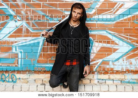 Stylish Handsome Man With A Bat Is Posing Near Brick Wall With Graffiti.