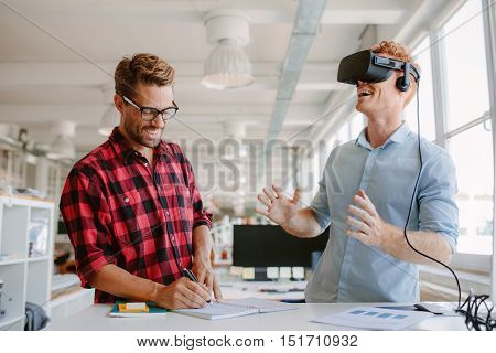 Shot of two young man standing at a table with VR goggles and writing on notepad. Developers testing virtual reality glasses in office.
