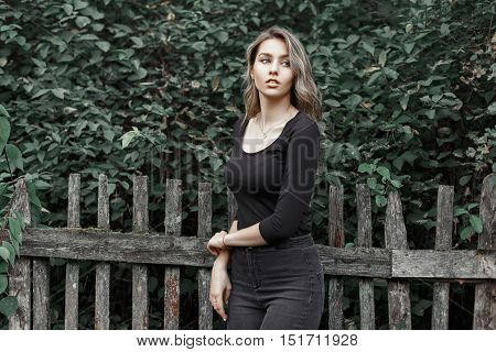 Beautiful Girl In A Black T-shirt Near The Wooden Fence On The Background Of Foliage