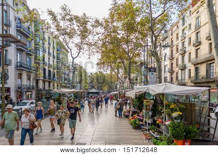 BARCELONA, SPAIN - SEPTEMBER 21. Tourists and residents strolls along the Ramla de San Josep on a sunny day in autumn. Florist offers flowers in all colors in Barcelona on September 21, 2016
