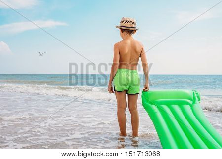 Boy stands with swimming air mattress on the sea surf line