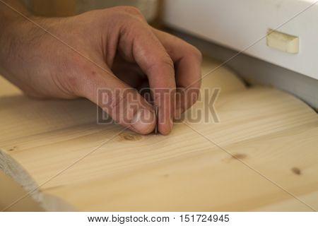 Hammer and Nail Using hammer and nail on wood and bokeh background