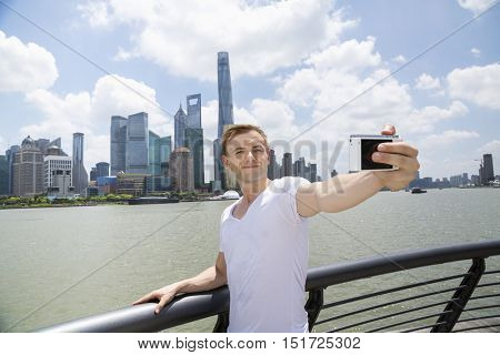 Mid adult man taking selfie while standing by railing against Pudong skyline