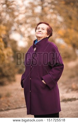 Senior woman 70-75 year old wearing winter jacket outdoors. Looking away.