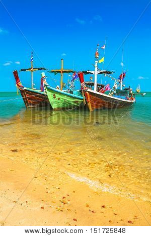 Colored fishing boats in the sea in the turquoise waters at sandy shores