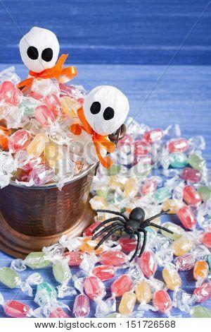 Halloween candy bucket lollipop ghosts and rubber spider on purple wooden backround vertical orientation