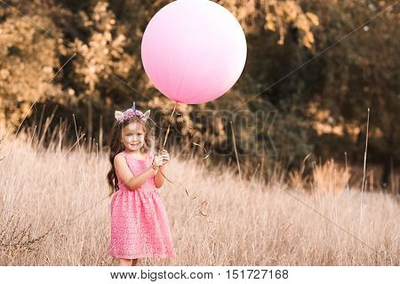 Stylish baby girl 4-5 year old holding big balloon wearing trendy pink dress in meadow. Playful. Birthday party.
