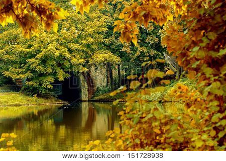 A beautiful autumn park with colorful reflections in the waterand an arch.