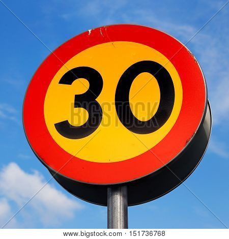 Swedish road sign with black letters on a yellow background with red frame against blue sky indicates that the speed is limited to a maximum of 30 km / h The sign usually occurs at schools and in residential areas.