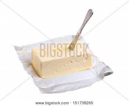 A pack of margarine that is opened on a white background with an inserted butter knife.