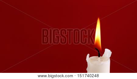 The top of a white burning candle with a flame on red background with emty space.