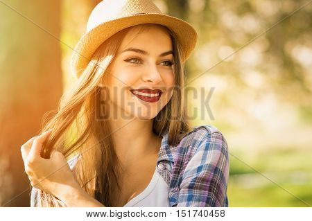 Closeup portrait of beautiful young blonde Caucasian woman in park in autumn smiling, wearing fedora, dark lipstick and checkered shirt. Vibrant colors, medium retouch.