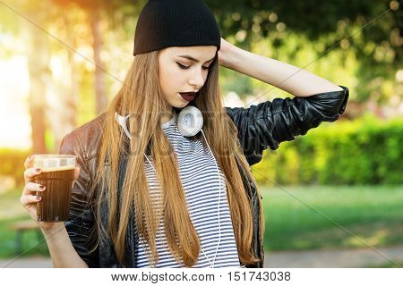 Cool young blonde Caucasian woman in dark lipstick, beanie hat, leather jacket holding a glass of dark beer, outdoors in park on sunny day. Modern millennial teenage girl in urban outfit.