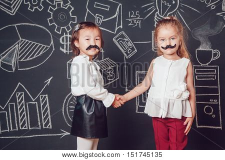 Two little girls as with mustache standing on dark background of painted wall. They shake hands