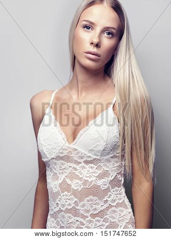 Portrait of young woman in nightwear standing over gray background