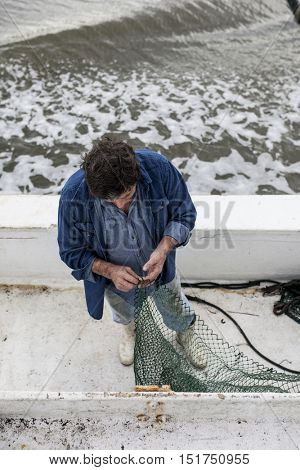 BEAUFORT, SOUTH CAROLINA-OCTOBER 15, 2015: Commercial fisherman mends his net aboard a fishing vessel off the coast of South Carolina