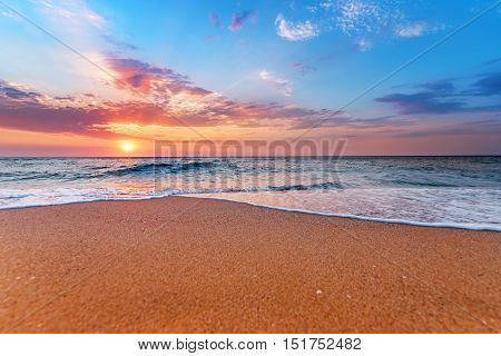 Brilliant ocean beach sunrise. Golden sands and blue sky